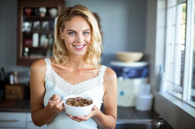 Ritratto di giovane donna che mangia prima colazione in cucina
