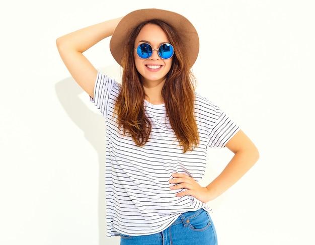 Ritratto di giovane donna che ride elegante modello in abiti casual estivi in cappello marrone isolato sul muro bianco