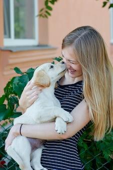 Ritratto di giovane donna che tiene sulle mani cucciolo labrador