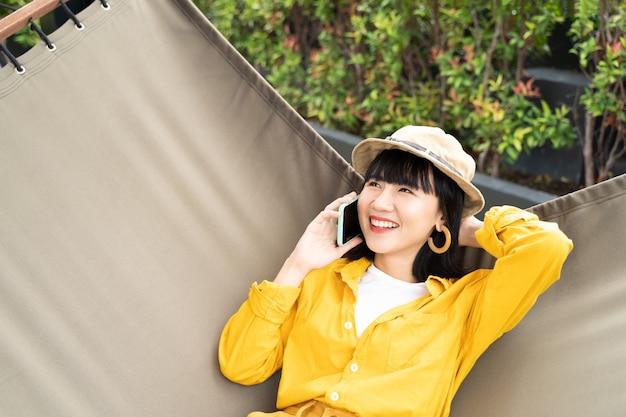 Ritratto di giovane donna che usando cellulare con felice e rilassato a casa