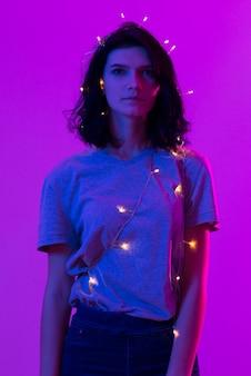 Ritratto di giovane donna con appendere le luci di natale sul suo corpo