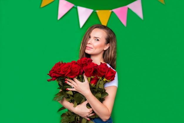 Ritratto di giovane donna con bouquet di rose rosse su sfondo verde con spazio di copia.