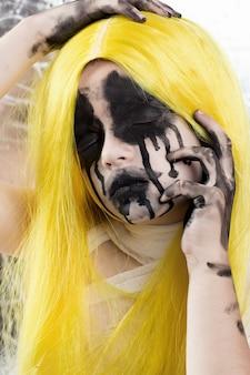 Ritratto di giovane donna con i capelli gialli con il trucco spaventoso di halloween