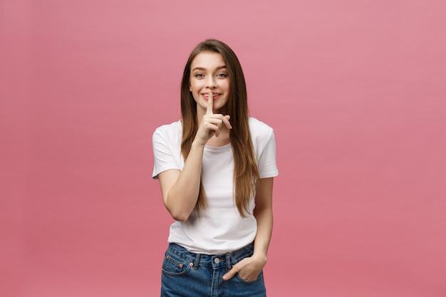 Ritratto di giovane donna con il dito sulle labbra contro il muro rosa