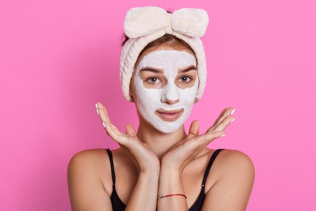 Ritratto di giovane donna con maschera facciale all'argilla, ha cerchietto bianco intorno alla testa