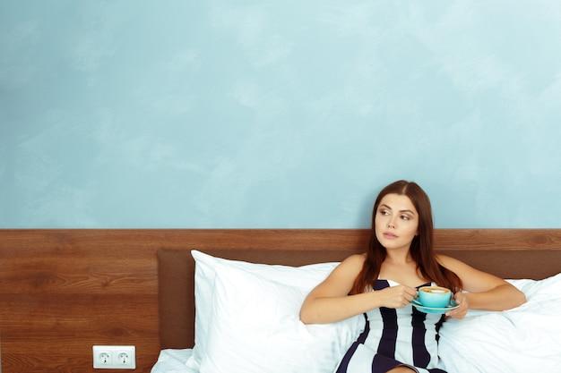 Ritratto di giovane donna con una tazza di caffè o tè a letto