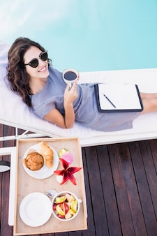Ritratto di giovane donna con una tazza di tè e relax su una sdraio vicino a bordo piscina