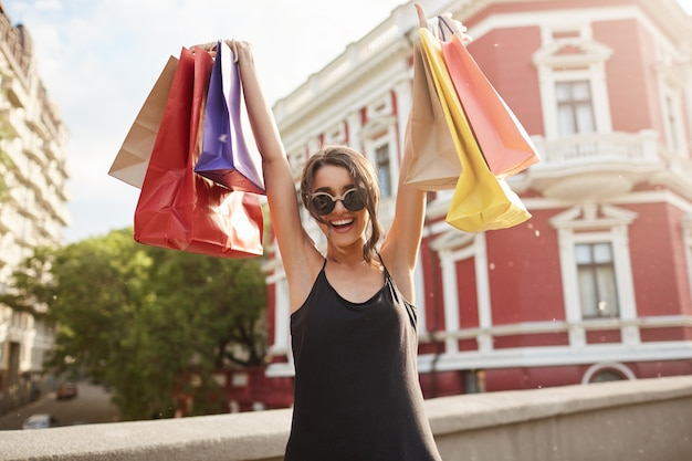 Ritratto di giovane donna dai capelli scuri in occhiali da sole e abiti neri in possesso di sacchetti colorati