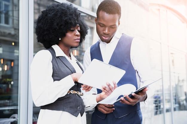Ritratto di giovane donna di affari africana che mostra qualcosa sulla compressa digitale al suo collega