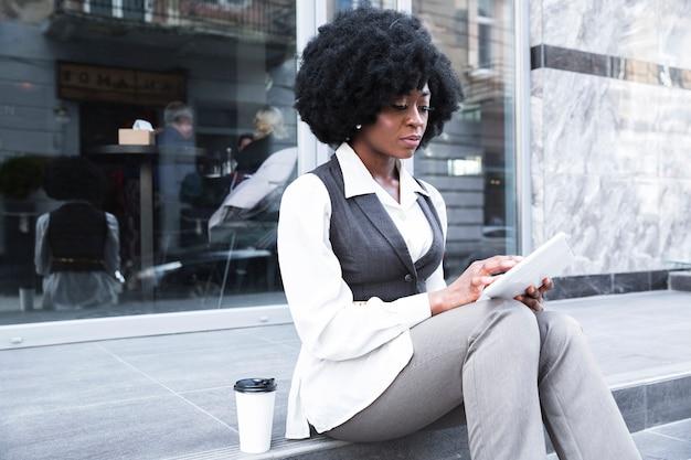 Ritratto di giovane donna di affari africana che si siede fuori dell'ufficio facendo uso della compressa digitale