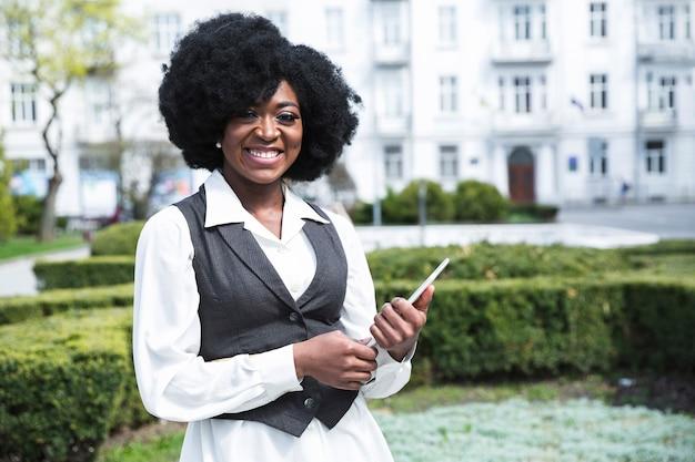 Ritratto di giovane donna di affari africana sorridente che tiene compressa digitale