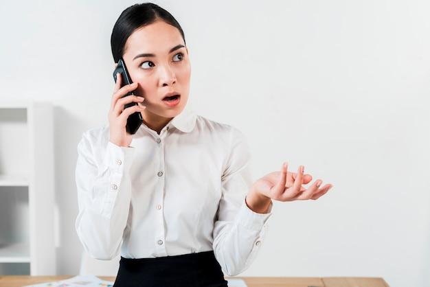 Ritratto di giovane donna di affari che discute sul gesturing del telefono cellulare