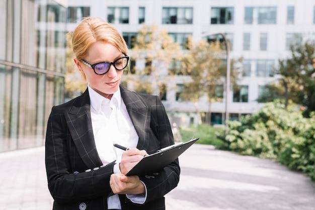Ritratto di giovane donna di affari che scrive sulla lavagna per appunti con la penna