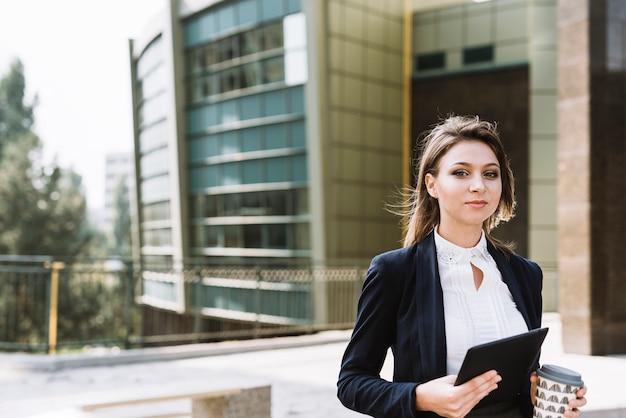 Ritratto di giovane donna di affari che tiene compressa digitale e tazza di caffè asportabile a all'aperto