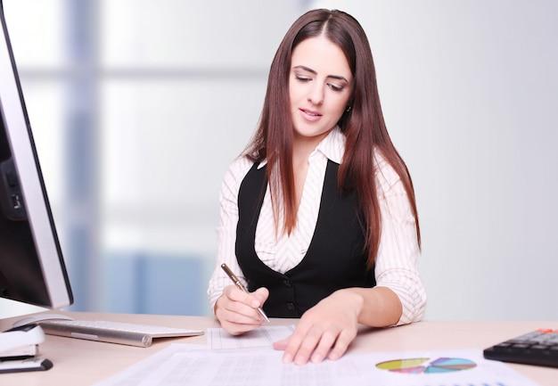 Ritratto di giovane donna di affari felice sitting at desk che calcola finanza