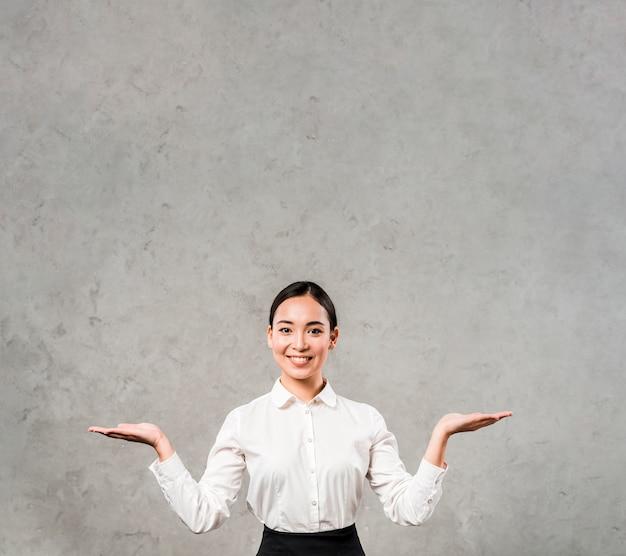 Ritratto di giovane donna di affari sorridente che scrolla le spalle contro il muro di cemento grigio