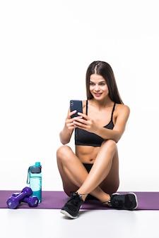 Ritratto di giovane donna di forma fisica che si siede sul pavimento e che usando smarpthone i su un bianco
