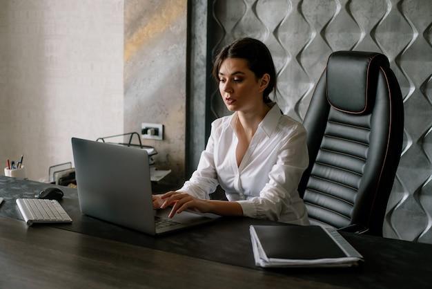 Ritratto di giovane donna di impiegato seduto alla scrivania in ufficio utilizzando il computer portatile cercando occupato con espressione seria e fiduciosa sul viso che lavora in ufficio