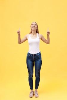 Ritratto di giovane donna di successo che celebra la sua vittoria. isolato su sfondo giallo