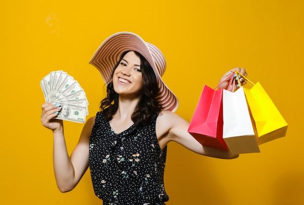Ritratto di giovane donna elegante allegra in occhiali da sole e cappello in possesso di denaro e sacchetti colorati isolati su sfondo giallo