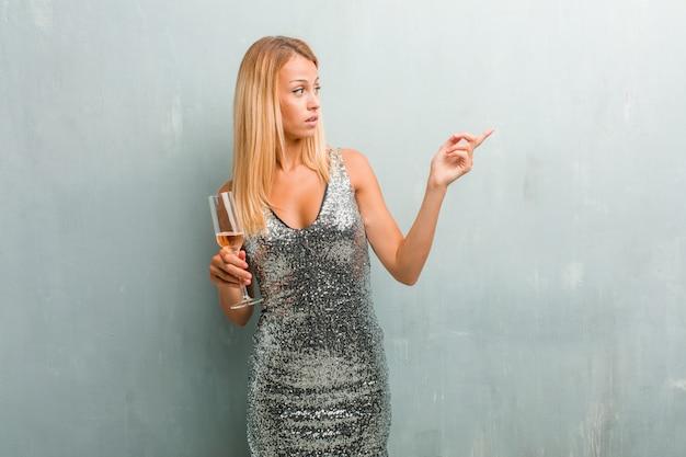 Ritratto di giovane donna elegante bionda che punta verso il lato, sorridente sorpreso presentare qualcosa, naturale e informale. in possesso di un bicchiere di champagne.