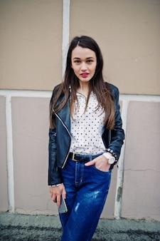 Ritratto di giovane donna elegante che indossa giacca di pelle con il telefono cellulare a portata di mano