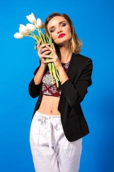 Ritratto di giovane donna elegante con trucco luminoso e blazer scuro, che tiene i fiori bianchi