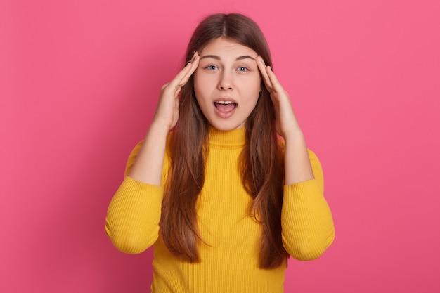 Ritratto di giovane donna emotiva scioccata che apre la bocca e gli occhi ampiamente, mettendo le mani sulle tempie, mal di testa, stress, sensazione di dolore, problemi di salute. concetto di persone e stress.