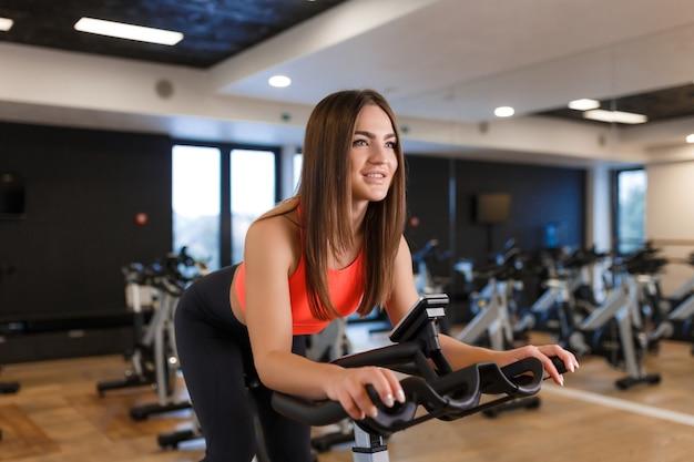 Ritratto di giovane donna esile in allenamento sportwear sulla cyclette in palestra. stile di vita sportivo e benessere