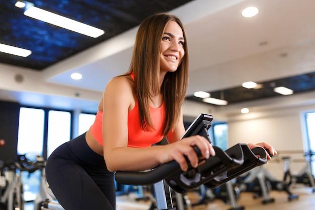 Ritratto di giovane donna esile in allenamento sportwear sulla cyclette in palestra.