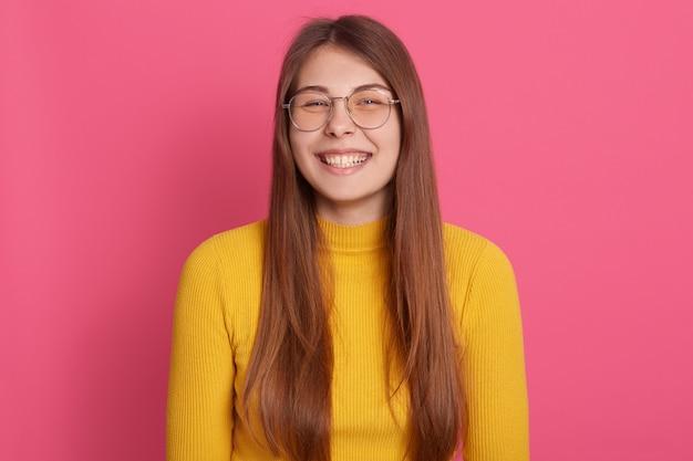 Ritratto di giovane donna felice che sta contro la parete rosa. femmina caucasica in casual e occhiali
