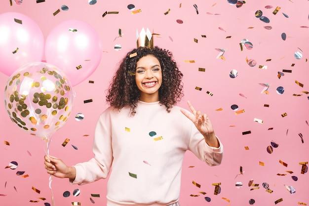 Ritratto di giovane donna felice con t-shirt rosa con palloncini colorati e coriandoli