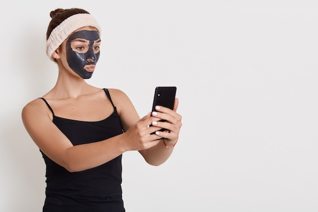 Ritratto di giovane donna felice dopo la doccia con fascia per capelli in testa, con maschera nera, si erge su un muro bianco, prendendo selfie tramite il suo telefono cellulare.