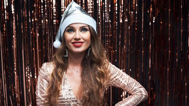Ritratto di giovane donna felice in argento cappello santa e abito elegante.