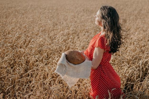 Ritratto di giovane donna felice in vestito rosso che tiene il pane di segale rustico sul fondo del sole del giacimento di grano
