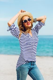 Ritratto di giovane donna fresca in occhiali da sole freschi e cappello di paglia in posa sulla soleggiata spiaggia tropicale