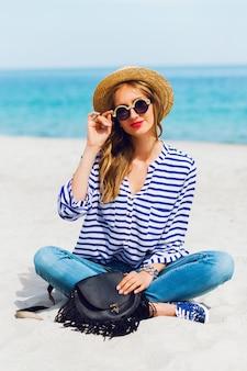 Ritratto di giovane donna fresca in occhiali da sole freschi e cappello di paglia seduto sulla soleggiata spiaggia tropicale