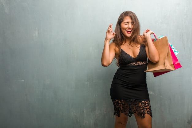 Ritratto di giovane donna graziosa che indossa un abito contro un muro che attraversa le dita