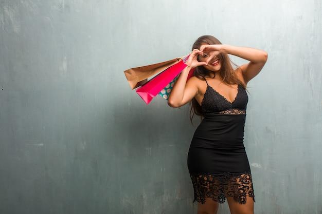 Ritratto di giovane donna graziosa che indossa un abito contro un muro facendo un cuore con le mani