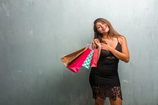 Ritratto di giovane donna graziosa che indossa un abito contro un muro facendo un gesto romantico