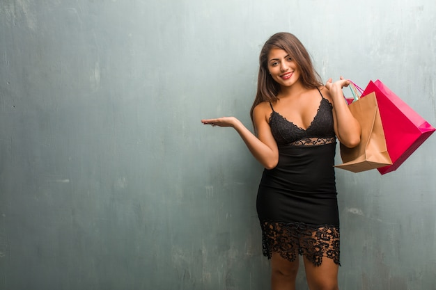 Ritratto di giovane donna graziosa che indossa un abito contro un muro in mano qualcosa con le mani
