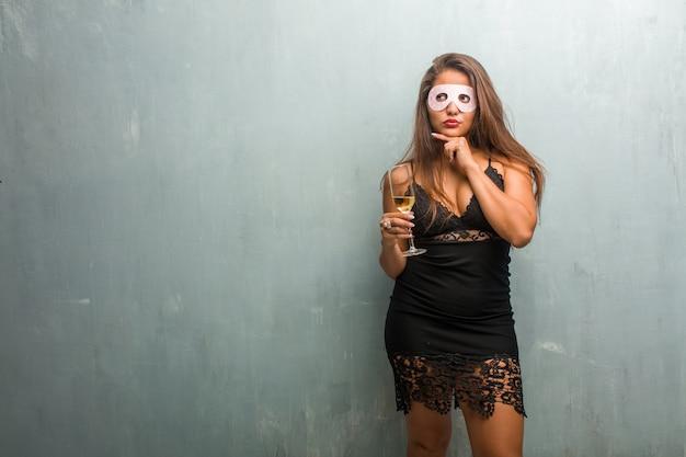 Ritratto di giovane donna graziosa che indossa un abito contro un muro, pensando e alzando lo sguardo