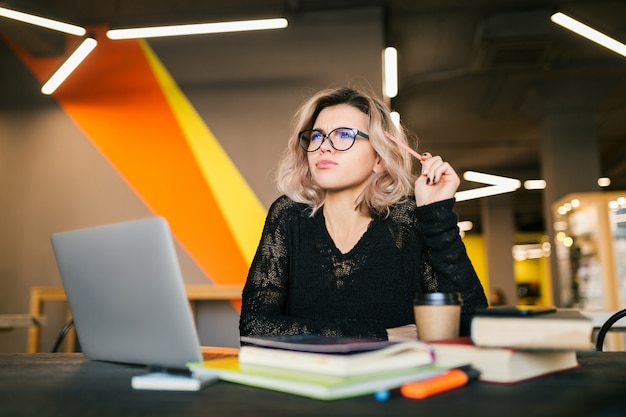 Ritratto di giovane donna graziosa che si siede al tavolo in camicia nera che lavora al computer portatile in ufficio di co-working, con gli occhiali, pensando al problema