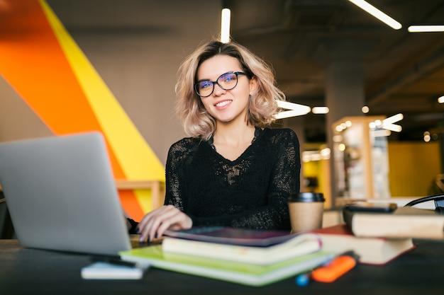Ritratto di giovane donna graziosa che si siede al tavolo in camicia nera che lavora al computer portatile in ufficio di co-working, con gli occhiali, sorridente, felice, positivo