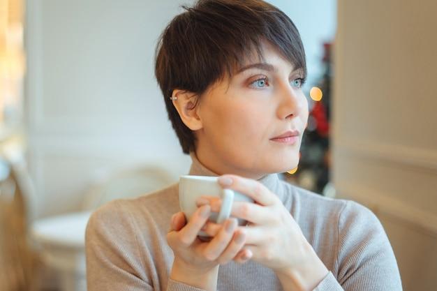 Ritratto di giovane donna graziosa con i capelli corti, bere il caffè nella caffetteria