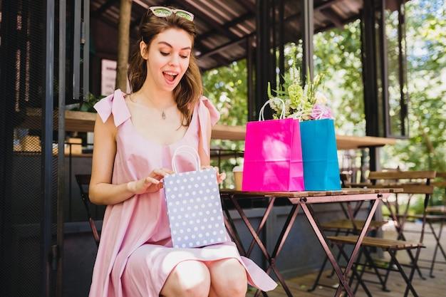 Ritratto di giovane donna graziosa felice sorridente con espressione del viso sorpreso seduto nella caffetteria con borse della spesa, abito di moda estiva, abito di cotone rosa, abbigliamento alla moda