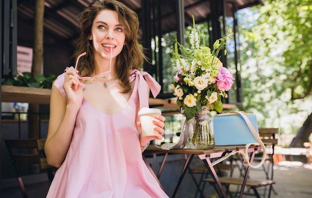 Ritratto di giovane donna graziosa felice sorridente con seduta in caffè bere caffè, vestito di moda estiva, stile hipster, vestito di cotone rosa, accessori di abbigliamento alla moda