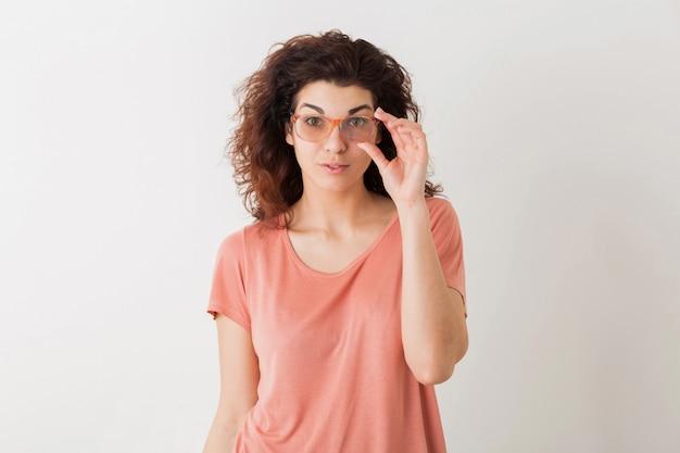 Ritratto di giovane donna graziosa naturale con l'acconciatura riccia in camicia rosa che posa i vetri da portare isolati, espressione sorpresa del fronte