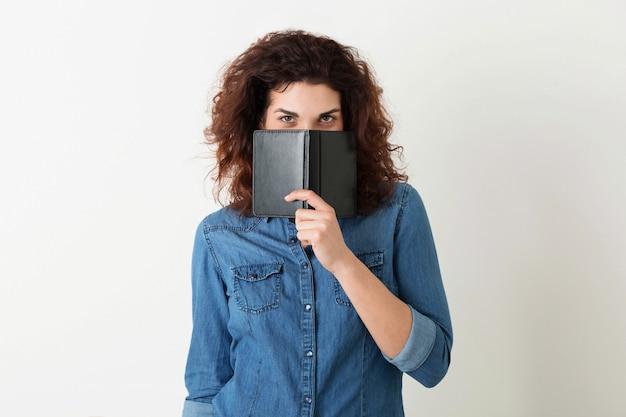 Ritratto di giovane donna graziosa sorridente naturale con l'acconciatura riccia in camicia di jeans che posa con il taccuino isolato, apprendimento dello studente, nascondentesi fronte dietro il libro