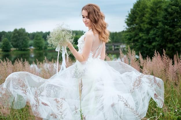 Ritratto di giovane donna graziosa (sposa) in abito da sposa bianco all'aperto, acconciatura